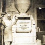 A production manager shows off the company's mixer, circa 1932.