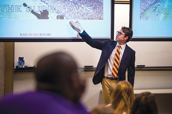 Management communication student Hamilton Beard explains his group's billboard during a presentation before representatives of the Greater New Orleans Sports Foundation.